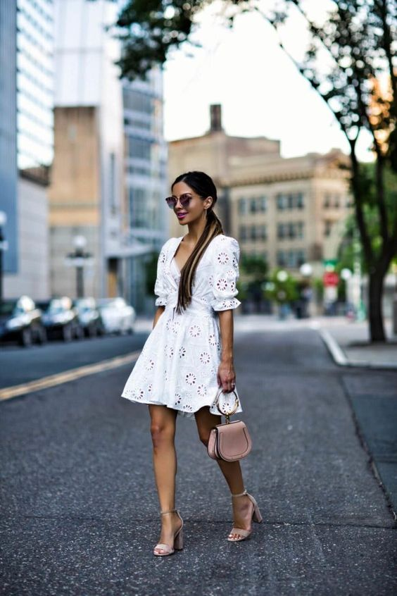 a boho lace A-line over the knee dress with a deep neckline, short sleeves, blush shoes and a blush bag