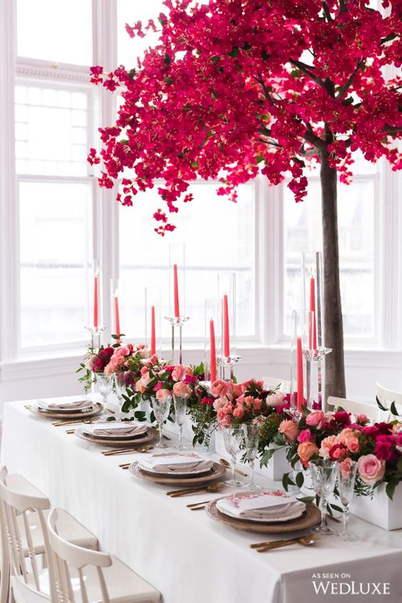 a bold Valentine's Day wedding table with lots of bold blooms, pink candles, a pink tree, gold cutlery and white porcelain