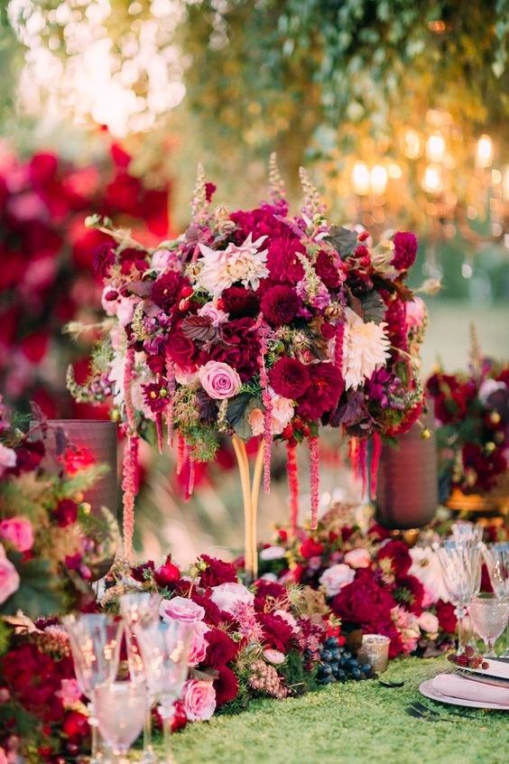 a bold and lush wedding centerpiece of blush, white and burgundy blooms and some leaves plus a matching table runner
