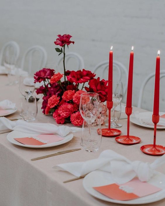 a bold and modern Valentine's Day wedding table with red candles in matching candleholders, a bold red and fuchsia floral arrangement, a blush tablecloth, silver cutlery