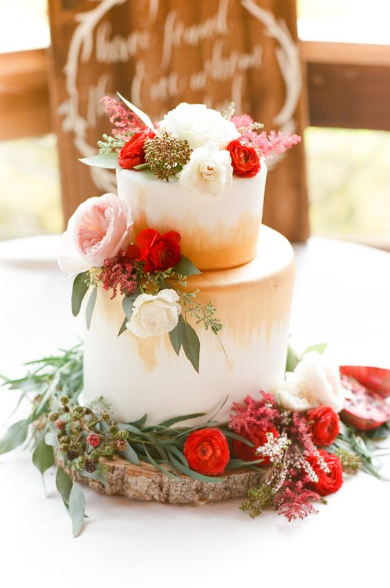 a bold modern Valentine wedding cake with gold touches, pink, red and white blooms, greenery and berries is a lovely idea