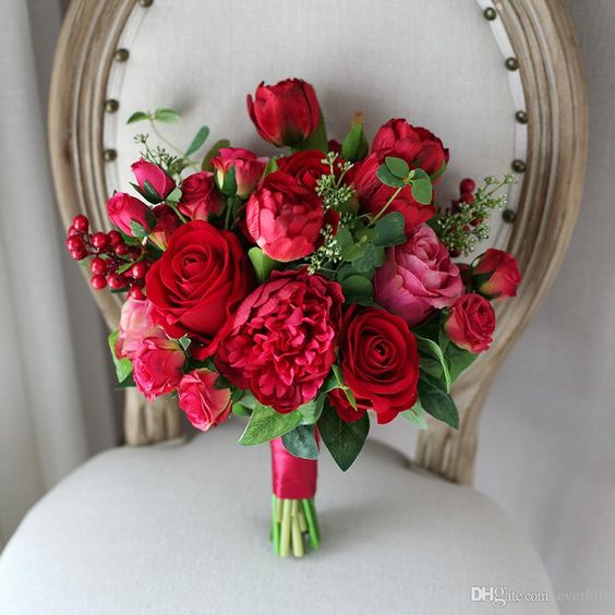 a bold red and pink rose bouquet with greenery and berries is a lovely and bright idea for a Valentine bride