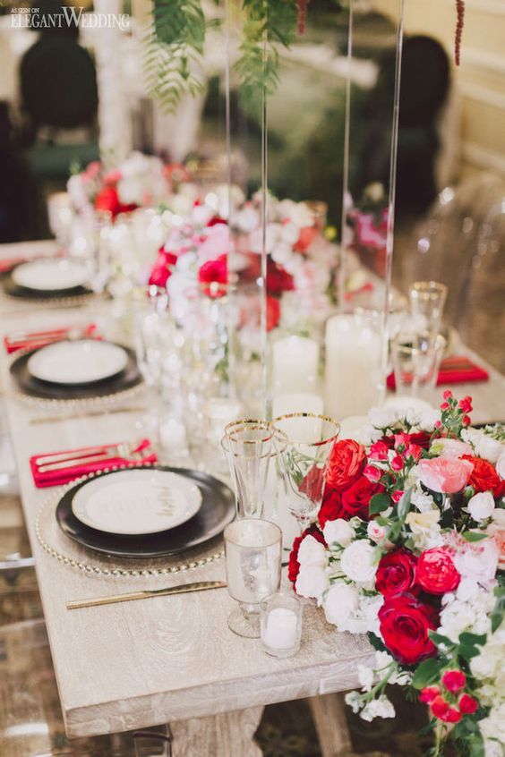a bright Valentine's Day wedding table with fuchsia napkins and blooms, gold rimmed glasses and gold cutlery, candles is wow