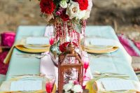 a bright and bold Valentine's Day wedding table with bold blooms, a candle lantern, gold chargers and colorful glasses
