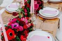 a bright and chic Valentine's Day wedding table with red, fuchsia, burgundy blooms, blush candles and menus, gold cutlery and gold candleholders