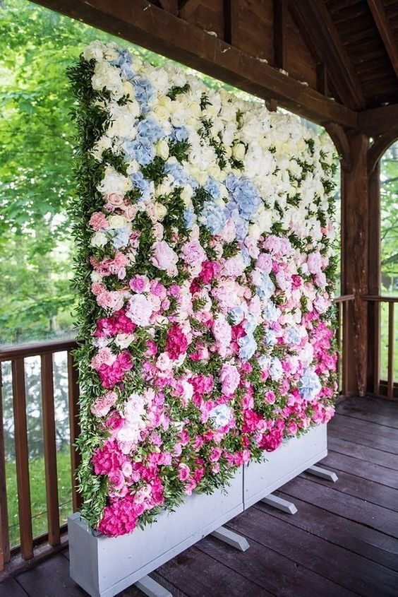 a bright floral wall in white, pink and pink plus textural greenery as a ceremony and photo booth wedding backdrop