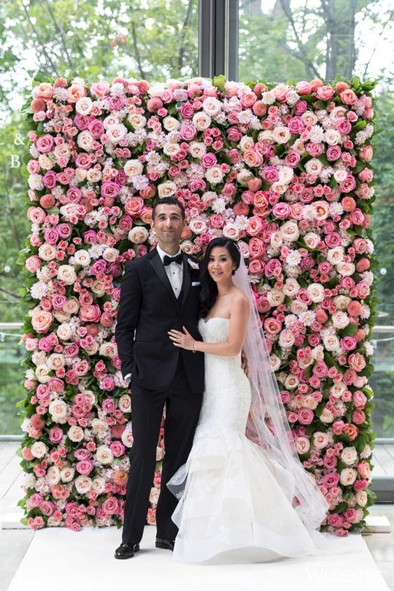 a bright pink and blush flower wall is a chic and bold wedding backdrop idea that is timeless