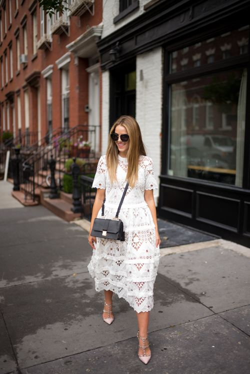 a catchy and romantic A-line mini dress of lace, with a high neckline, short sleeves, a black mini bag and blush spiked heels