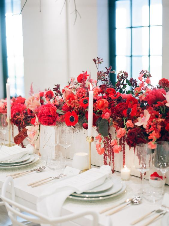a chic and gorgeous Valentine's Day wedding table with gold candleholders, white porcelain, linens and super bold red and pink blooms