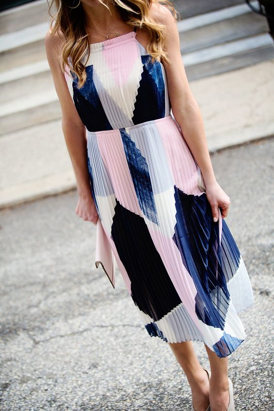 a chic modern pleated midi dress with an abstract print in navy and pink, white shoes and a white clutch