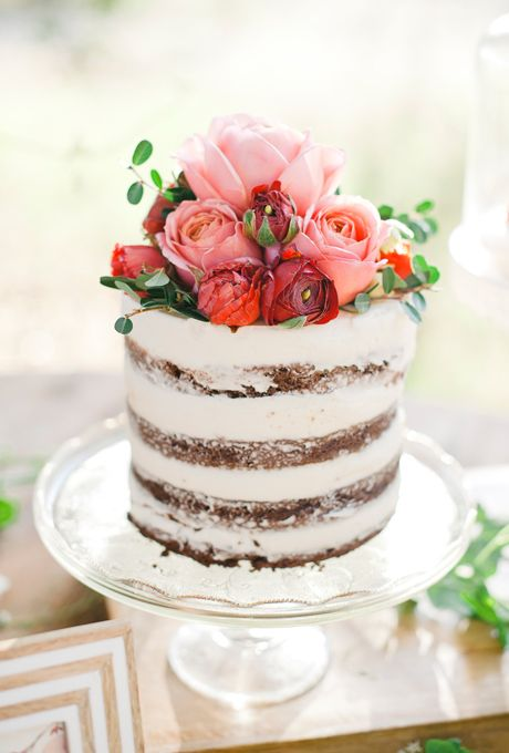 a chic naked wedding cake topped with red, pink and burgundy blooms and greenery for a Valentine wedding
