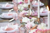 a chic pink Valentine's Day wedding tablescape with white and pink blooms, candles, pink plates, pink menus and cards