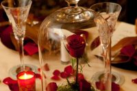 a cloche with a red roses and petals and some grass inside plus candles in red and some petals on the table for a Valentine centerpiece