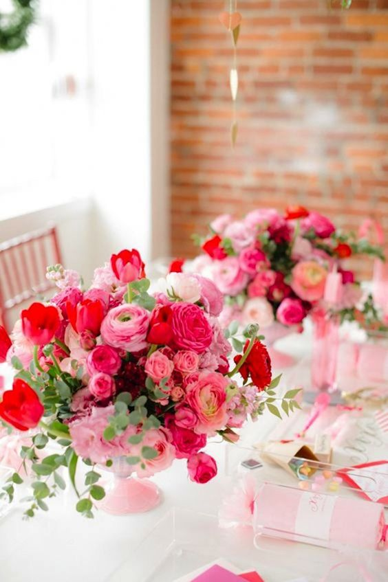 a colorful Valentine wedding centerpiece of pink, fuchsia and red blooms and foliage is a bold idea