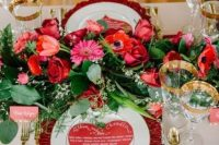 a colorful Valentine's Day wedding tablescape with a bold floral runner, gold rimmed glasses, gold cutlery and a pink chargrer