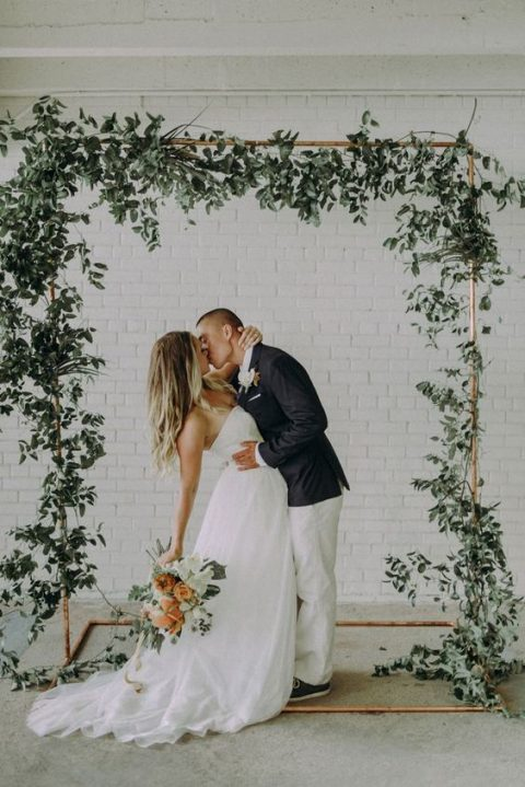 a copper wedding arch decorated with lush greenery is a elegant minimal idea for indoors or outdoors