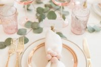 a cute and airy Valentine's Day wedding table with blush glasses, gold rimmed glasses, silver cutlery and greenery on the table