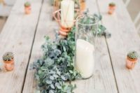 a cute greenery and foliage table runner with candles and copper canlde holders for a fresh wedding reception
