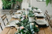 a eucalyptus table runner with succulents in pots, with pastel candles and tall white ones that match