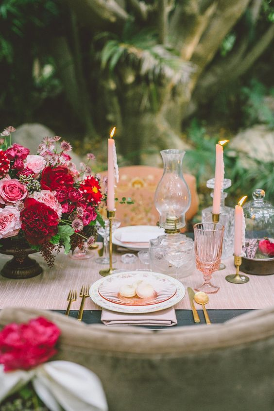 a fabulous Valentine's Day wedding table with a pink runner, candles and glasses, pink macarons, a bold floral centerpiece and candle lanterns