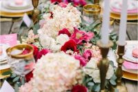 a fantastic Valentine's Day wedding table with pink and white blooms and greenery, white candles, pink menus and gold rimmed glasses
