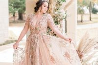 a fantastic blush A-line wedding dress with floral embroidery, short sleeves, a deep neckline and a train plus a crystal crown