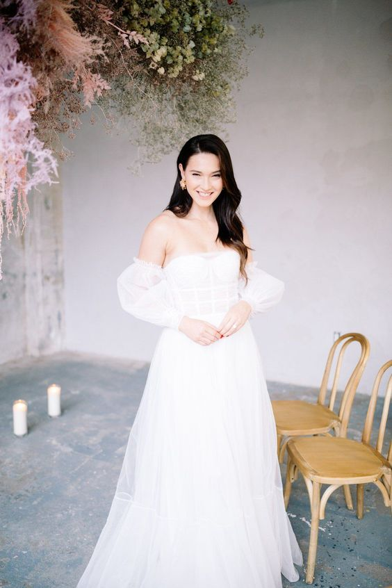 a feminine off the shoulder A-line wedding dress with a corset bodice, a layered skirt and puff sleeves is chic