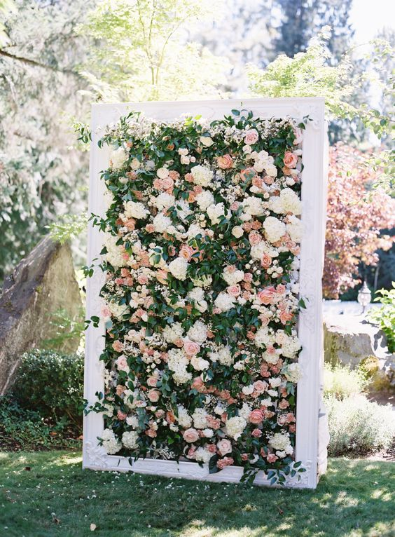 a floral wall backdrop with white and pink blooms, textural foliage in a white frame