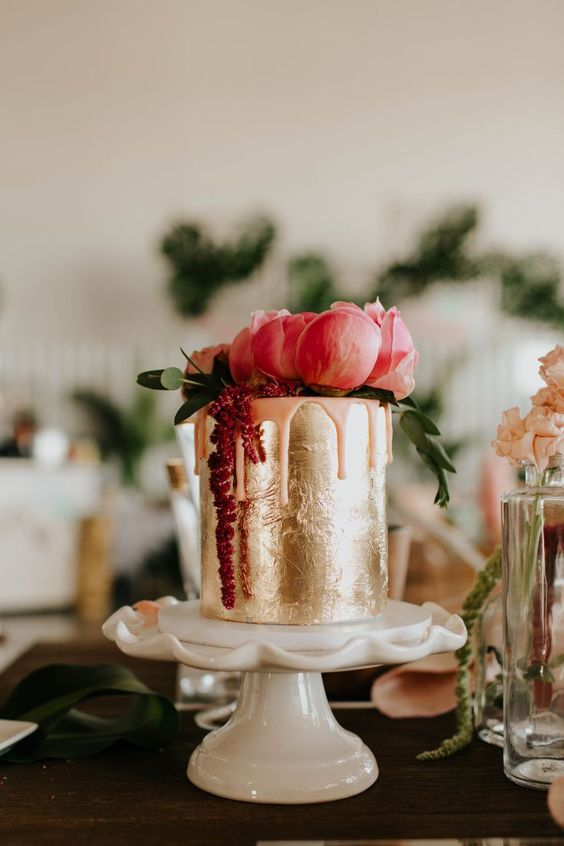 a gold foil wedding cake with pink dripping, pink and fuchsia blooms and greenery is a refined idea for a Valentine wedding