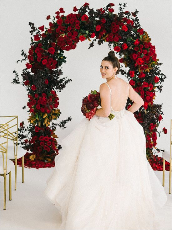 a gorgeous classic Valentine's Day wedding arch with red roses, greenery and magnolia leaves is a fantastic idea