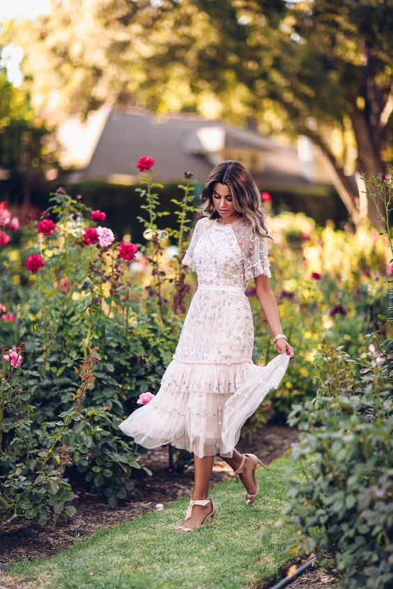 a gorgeous fully embellished A-line midi dress, a high neckline and short sleeves and a ruffle tier skirt