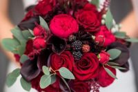 a gorgeous lush wedding bouquet of red roses, red peony roses, dark callas and greenery for a refined bridal bouquet