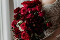 a gorgeous red rose wedding bouquet with greenery and berries is a stylish idea for a Valentine's Day bride