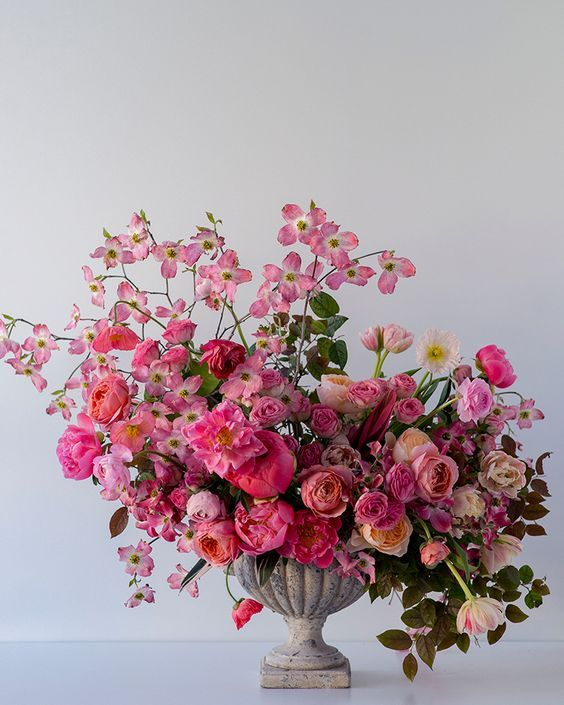 a gorgeous statement-like Valentine's Day wedding centerpiece of red, pink and neutral blooms and some greenery