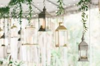a greenery garland with lanterns hanging on it as a reception decoration and greenery and white bloom centerpieces match this decor