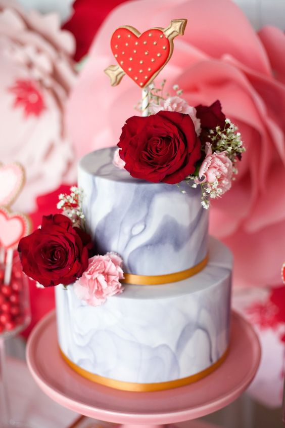 a grey marble wedding cake with gold ribbons, red and pink blooms and a red heart topper is adorable