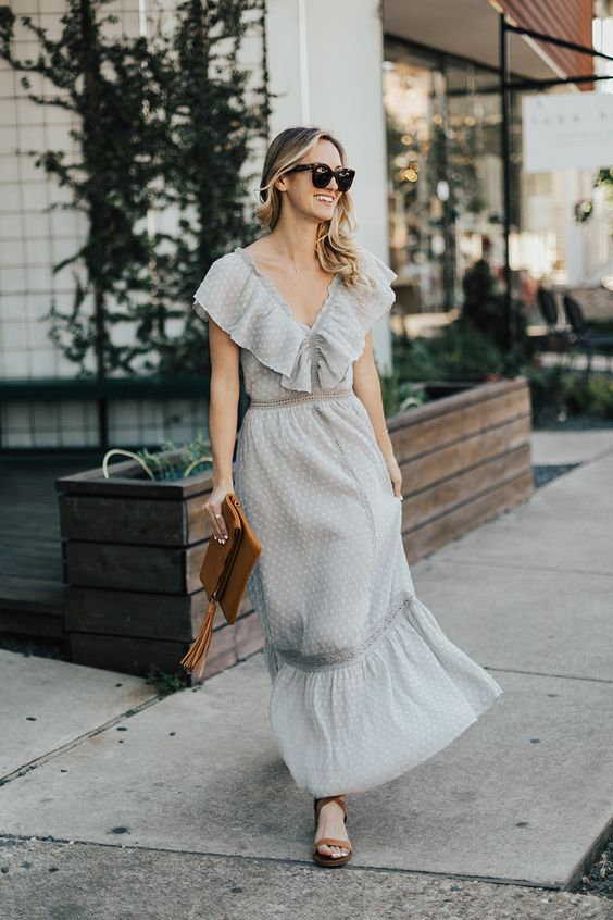 a grey polka dot maxi dress with ruffles, lace inserts, a brown clutch and brown strappy shoes