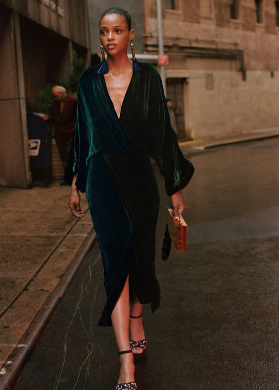 a hunter green midi dress with a pencil skirt, wide sleeves and a plunging neckline, embellished shoes, a mustard clutch and statement earrings