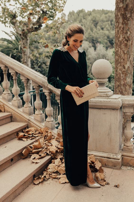 a hunter green velvet maxi dress with a V neckline, embellished shoulders, silver shoes and a clutch plus statement earrings