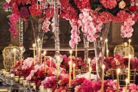a jaw-dropping Valentine's Day wedding table with bold pink, red and fuchsia blooms, gold candles, gold candleholders and chargers