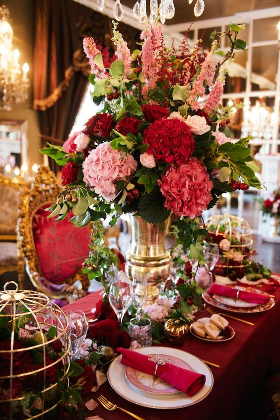 a lavish Valentine's Day wedding table with burgundy and fuchsia linens, a bold red and pink floral arrangement, cages with blooms