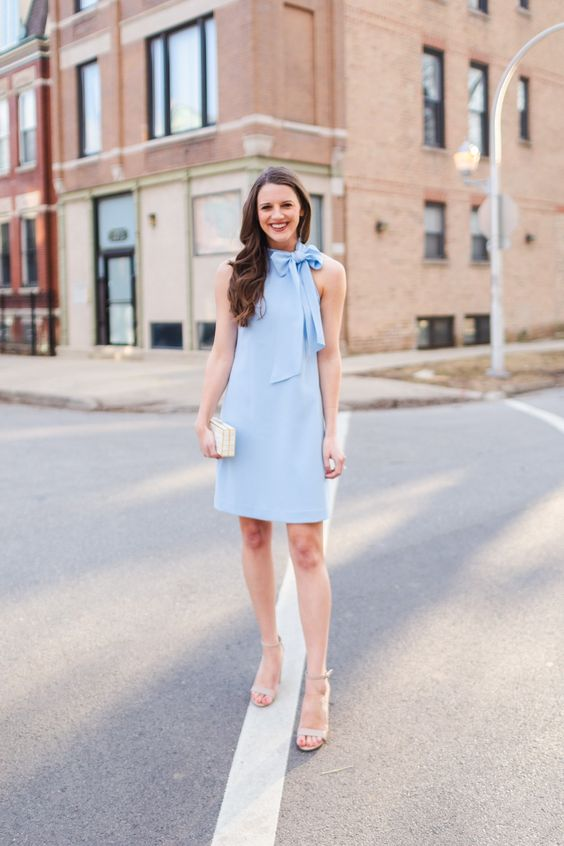 a light blue mini dress with a halter neckline, a bow, grey shoes and a nude box clutch for a spring wedding