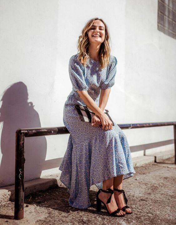 a light blue printed midi dress with an asymmetrical skirt, short sleeves, a high neckline, black shoes and a striped clutch