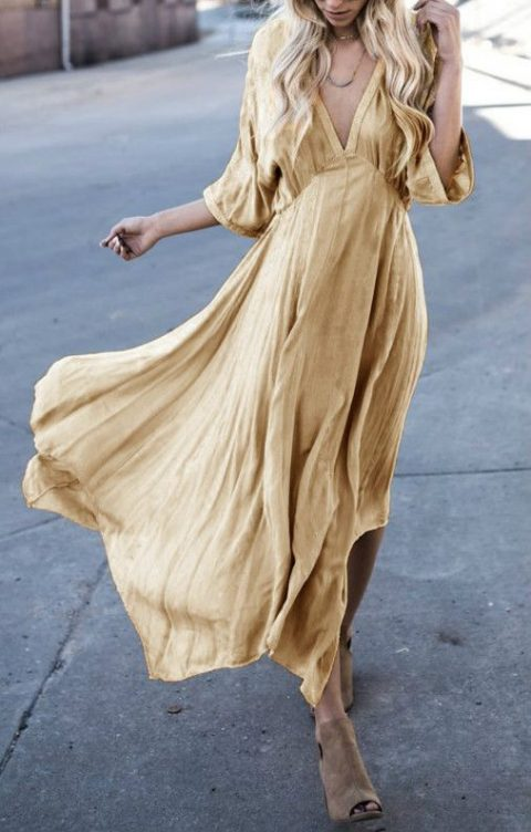 a loose fit pleated muted yellow dress with wide sleeves and a deep V-neckline plus brown peep toe booties