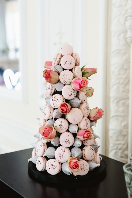 a lovely Valentine wedding cake of blush macarons, meringues and pink roses is gorgeous