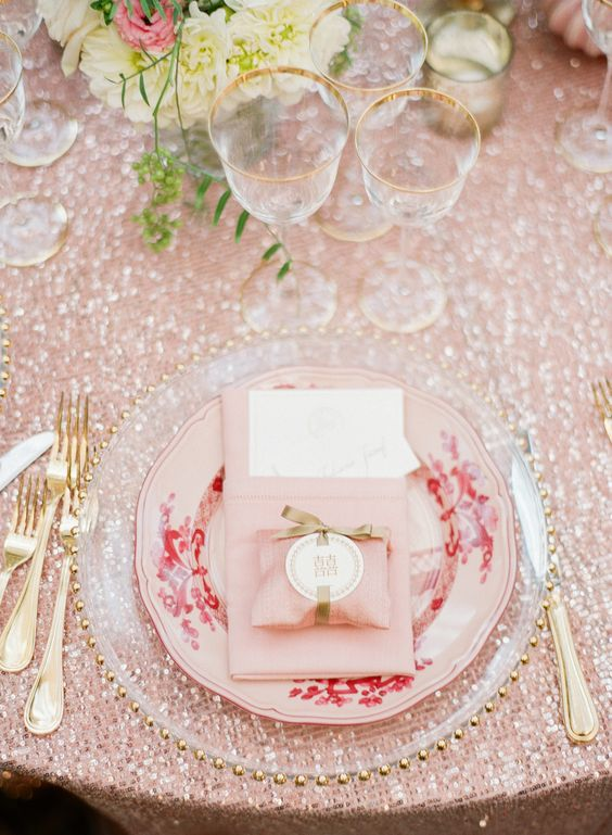 a lovely Valentine's Day wedding table with a pink sequin tablecloth, a pink and a sheer plate, gold rimmer glasses and gold cutlery