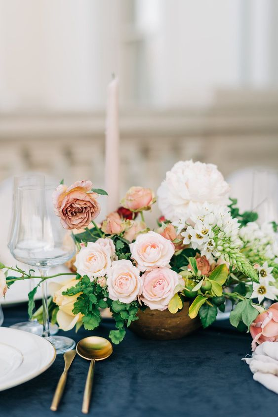 a lush Valentine wedding centerpiece of peachy, pink and white blooms and greenery is adorable and chic