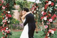 a lush and bold floral wedding arch covered with blush, pink and red roses and greenery is ideal for a Valentine wedding