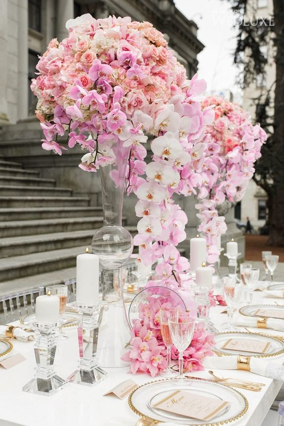 a lush and refined pink and blush floral wedding centerpiece on tall stands is very spectacular and it looks wow