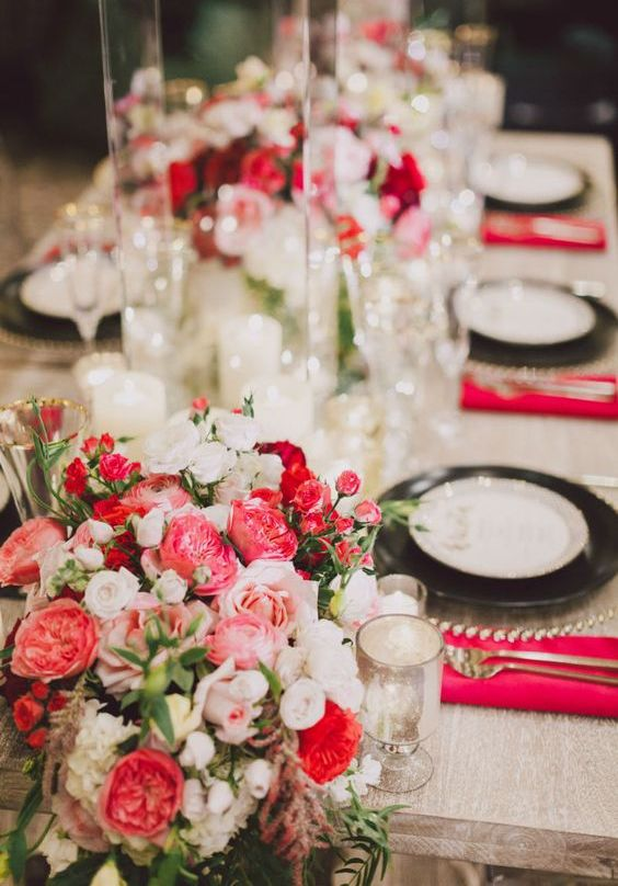 a lush floral centerpiece of blush, white, red blooms and greenery is a beautiful idea for a Valentine wedding